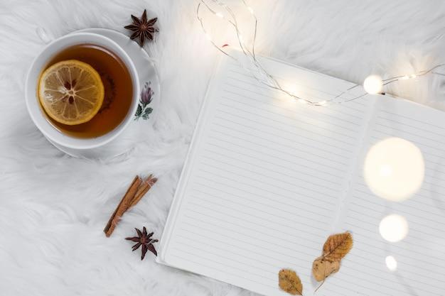 Teatime auf weißem pelzplaid mit notizbuch