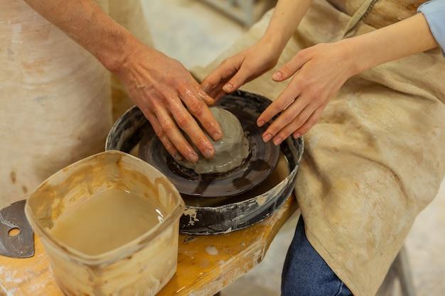 Technik der töpferscheibe. mädchen in schürze, die ton auf einem speziellen rad verarbeitet und mit klarem wasser benetzt
