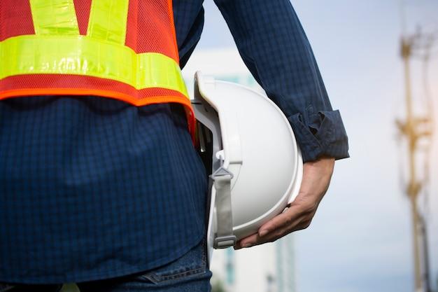 Technik hält weiße sicherheitshüte und elektrischen pfosten