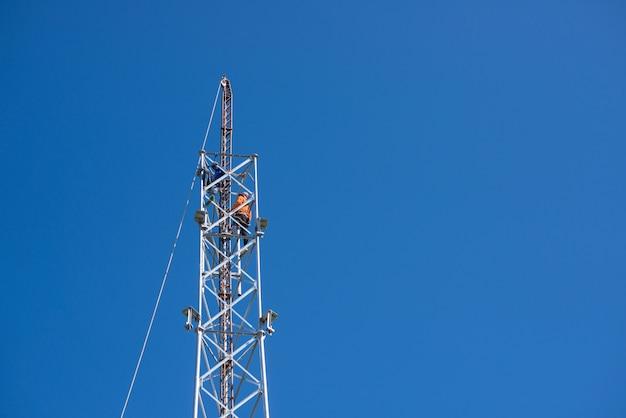 Techniker arbeiten an einem fernmeldeturm, der schmied arbeitete an einem telefonmast