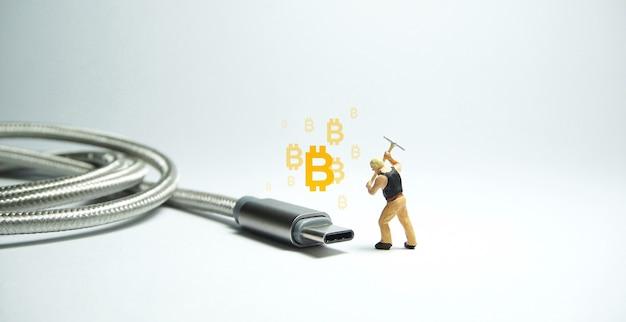 Techniker-arbeiterfigur, die vor usb-usb-typ-c-kabel steht. bitcoin-mining-konzept.