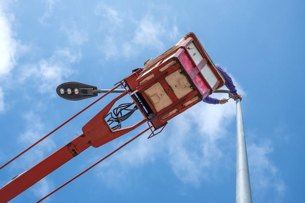 Techniker auf dem eimer-lkw hoch oben von einem kran, zum der straßenlaterne zu regeln.