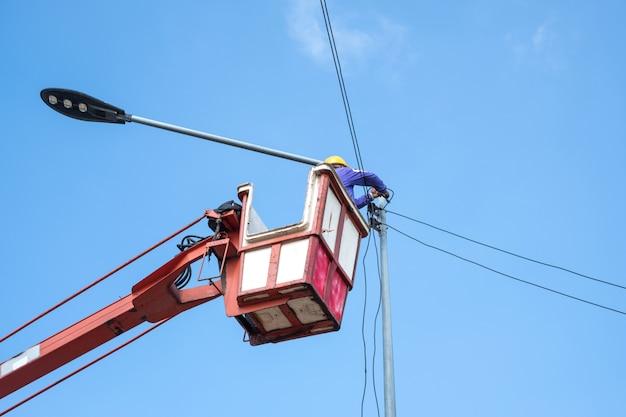 Techniker auf schaufelwagen hoch oben von einem kran, um straßenlaterne zu reparieren.