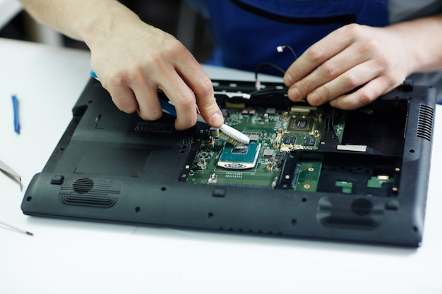 Techniker clearing circuit board des zerlegten laptops