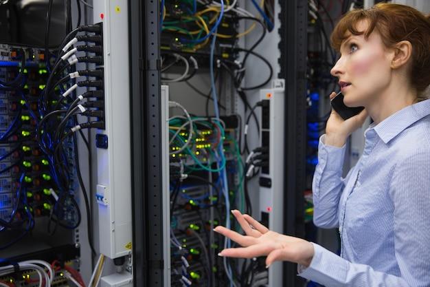 Techniker, der am telefon beim analysieren des servers spricht