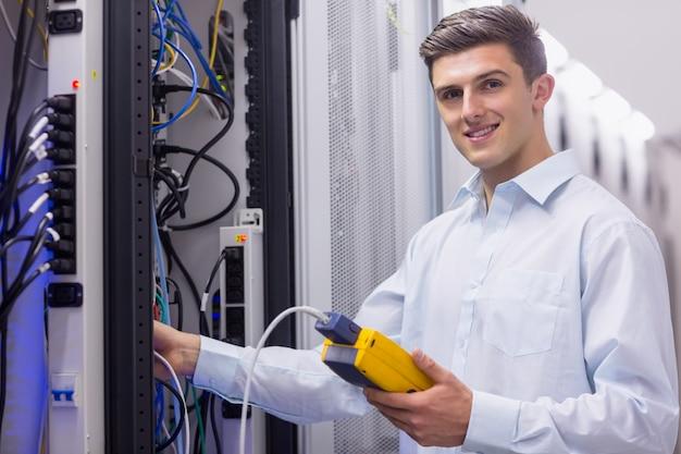 Techniker, der an der kamera beim reparieren des servers lächelt