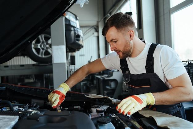 Techniker, der an der überprüfung und wartung des autos in der werkstatt arbeitet