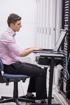 Techniker, der auf drehstuhl unter verwendung des laptops sitzt, um server zu bestimmen