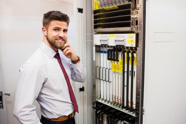 Techniker, der auf handy im serverraum spricht
