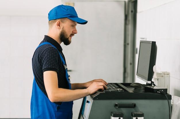 Techniker, der auf tastatur an der garage schreibt