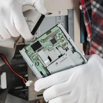 Techniker, der das ide-computerkabel in das festplattenlaufwerk einfügt