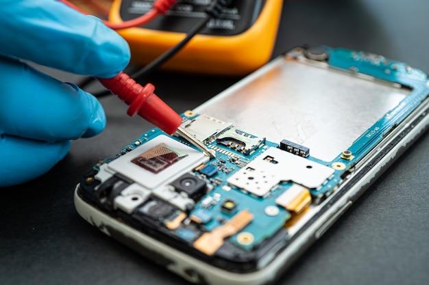 Techniker, der das innere des mobiltelefons durch lötkolben repariert repair
