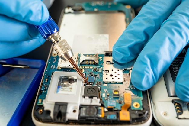 Techniker, der das innere des mobiltelefons durch lötkolben repariert