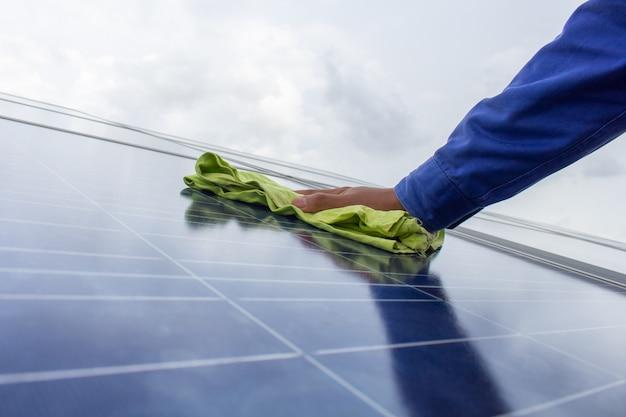 Techniker, der das tuch hält, um die solarzellenplatte abzuwischen