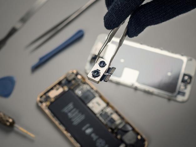 Techniker, der defekten smartphone auf schreibtisch repariert