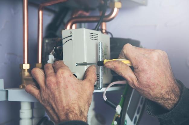 Techniker, der den gaskessel auf warmwasser und heizung wartet