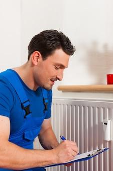 Techniker, der den wärmezähler liest