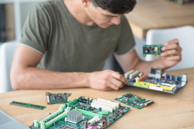Techniker, der die motherboardteile zusammenbaut