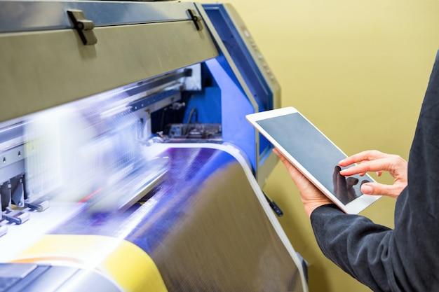 Techniker, der die tablet-steuerung mit großem tintenstrahldruck auf blauem vinyl verwendet