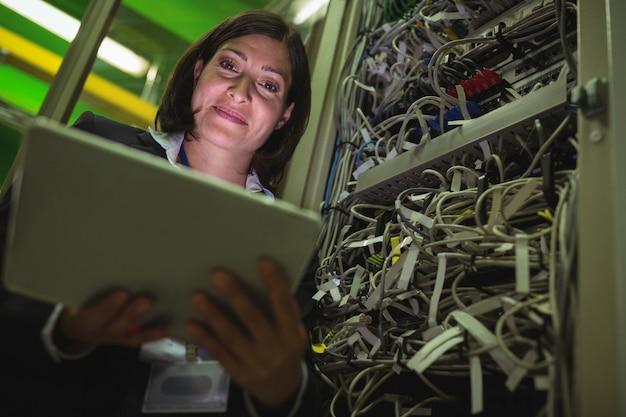 Techniker, der digitales tablet beim analysieren des servers verwendet
