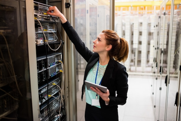 Techniker, der digitales tablett hält, während server untersucht
