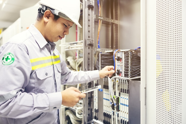 Techniker, der ein digitales tablet im serverraum verwendet, repariert das mainboard der karte und überprüft den netzwerkverbindungsstatus