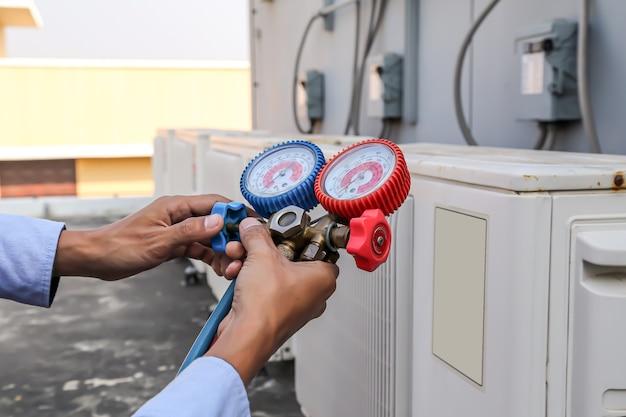Techniker, der eine krümmerlehre zum befüllen von außenklimageräten in industriefabriken verwendet.