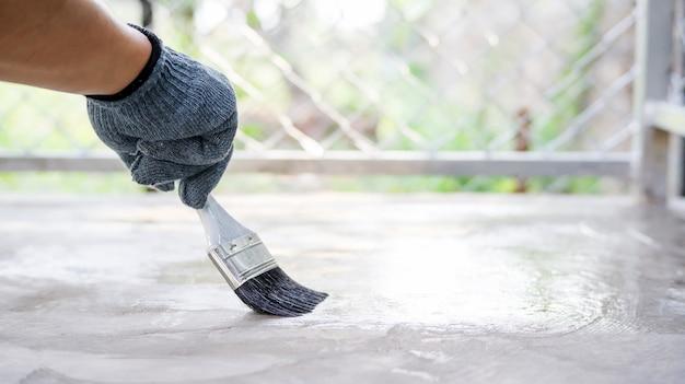 Techniker, der eine lackfarbe mit einem zementboden verwendet.