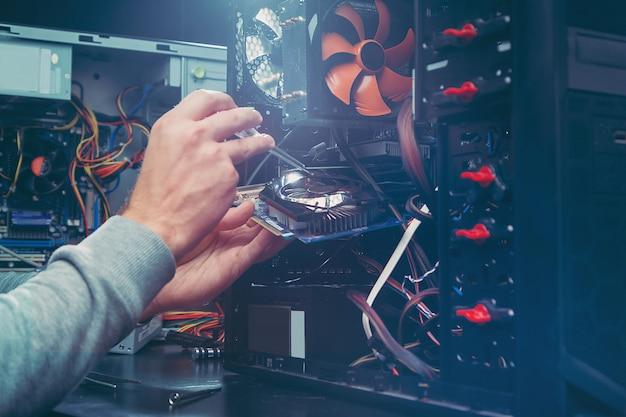 Techniker, der einen computer repariert, der prozess des ersetzens von komponenten auf dem motherboard.