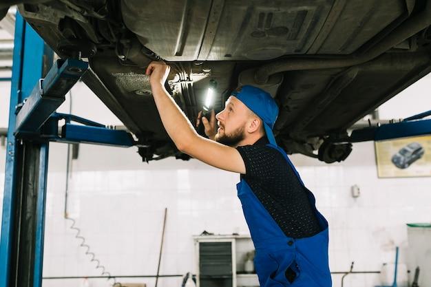 Techniker, der fahrzeugboden überprüft