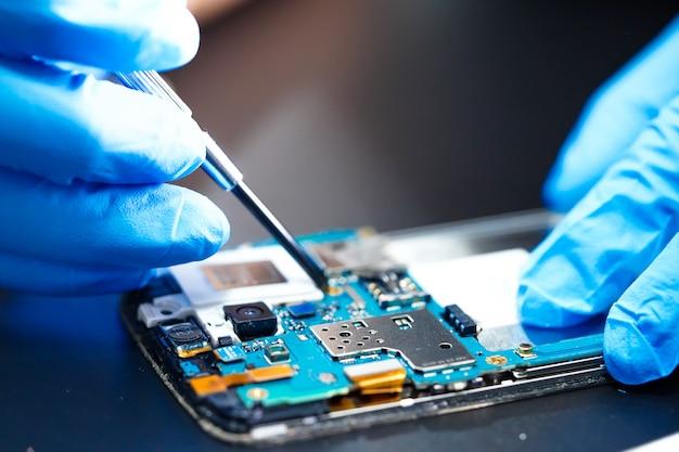 Techniker, der hauptplatine der mikroschaltung des smartphones repariert.