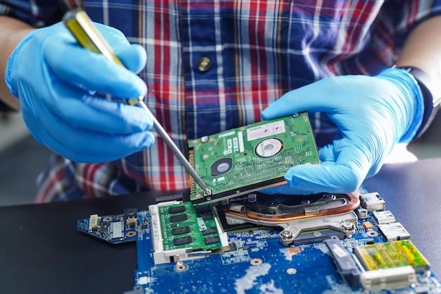 Techniker, der innerhalb der festplatte durch lötkolben repariert.