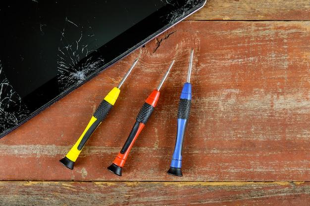 Techniker, der innerhalb der tablette durch schraubenzieher in der elektronischen reparaturtechnologie des handys repariert.