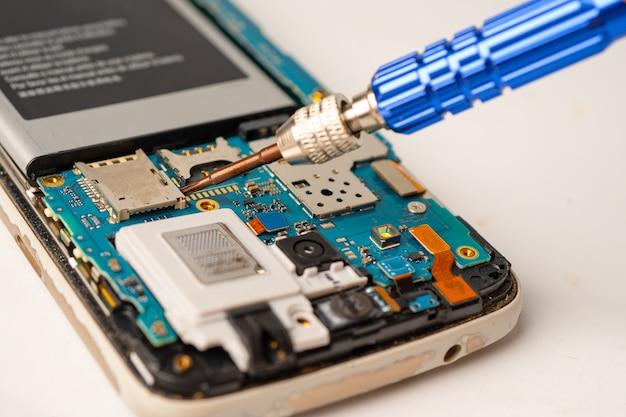 Techniker, der innerhalb des mobiltelefons durch lötkolben repariert