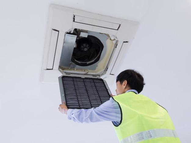 Techniker, der klimaanlage an der wand repariert.