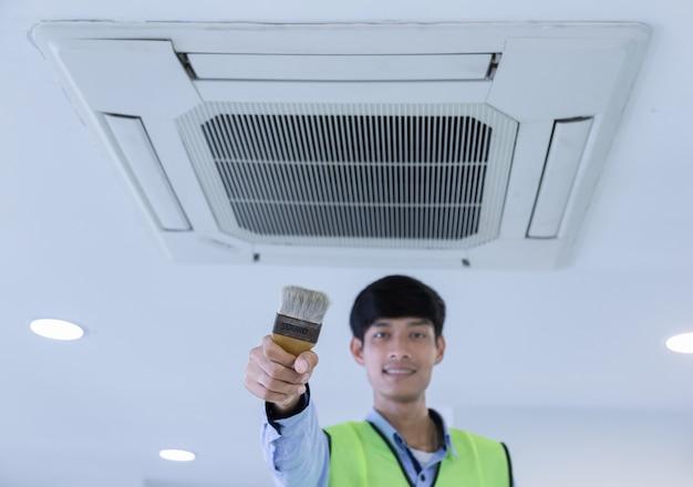 Techniker, der klimaanlage an der wand repariert