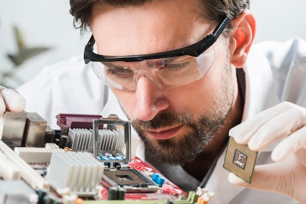Techniker, der mikrochipschlitz im computermotherboard überprüft