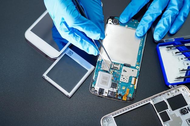 Techniker, der mikroschaltungshauptplatine von smartphone repariert.