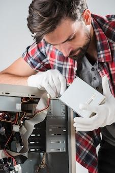 Techniker, der sata-datenkabel in das festplattenlaufwerk einsteckt