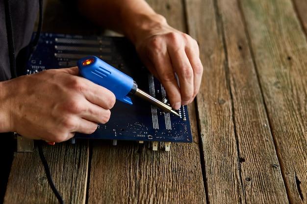 Techniker, der sich auf die reparatur der leiterplatte mit einem lötkolben konzentriert