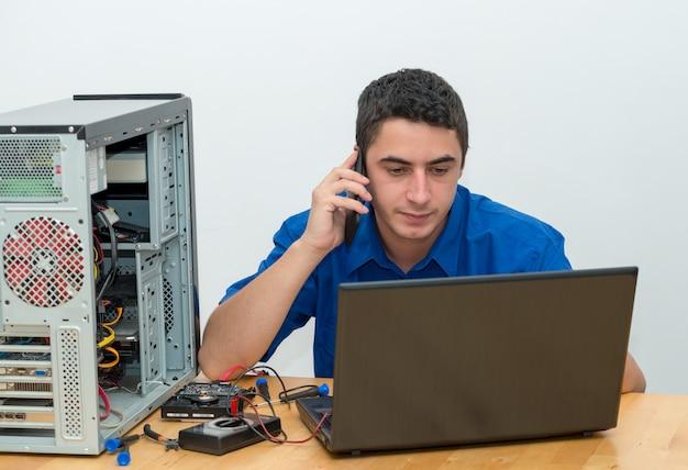 Techniker des jungen mannes, der an defektem computer arbeitet und den kunden anruft