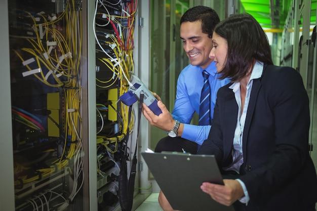 Techniker, die beim analysieren des servers einen digitalen kabelanalysator verwenden