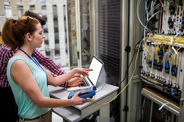 Techniker, die beim analysieren des servers einen laptop verwenden