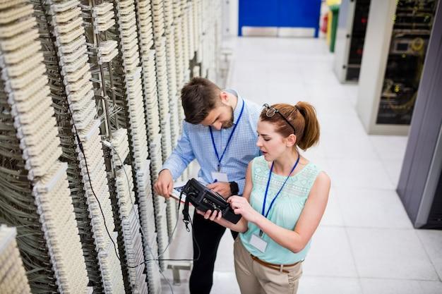 Techniker, die einen digitalen kabelanalysator verwenden