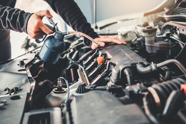 Techniker hands des automechanikers arbeitend in der autoreparatur