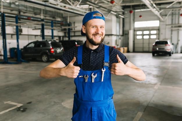 Techniker im overall mit schlüsseln an der werkstatt