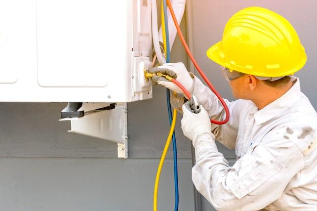 Techniker in normaler sicherheitskleidung, der den kompressor der klimaanlage überprüfen will