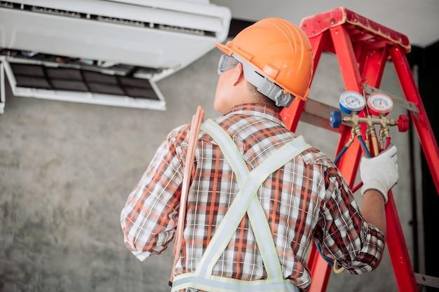 Techniker in normaler sicherheitskleidung überprüfen sie den kompressor der klimaanlage