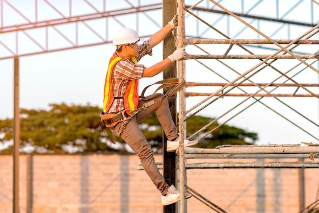Techniker in sicherheitskleidung klettert auf gerüste