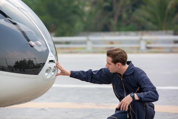 Techniker ingenieur, der vor privatem hubschrauber im flughafen steht
